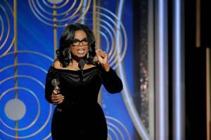 Oprah Winfrey speaking into a microphone will holding her Golden Globe award in her right hand.